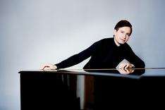 Alexey Sychev lehnt am Klavier
