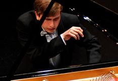 Alexey Sychev spielt Klavier, die rechte Hand ist in der Luft, die linke nicht sichtbar