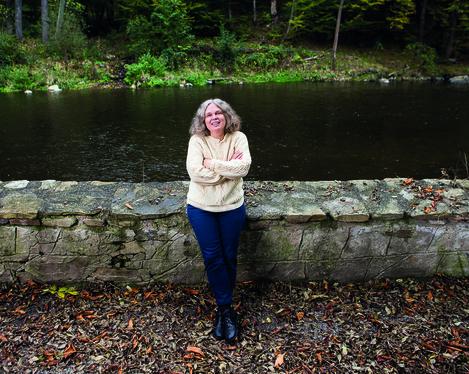 Die Komponistin Astrid Spitznagel lehnt an einer niedrigen Steinmauer. Im Hintergrund fließt ein Fluss. Das gegenüberliegende Ufer ist von einem Wald gesäumt.