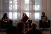 Foto: Bild vom Podium, auf dem drei Leute sitzen und lachen