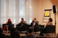 Foto aus dem Publikum auf das Podium, auf dem vier Leute sitzen und eine Person hat gerade ein Mikrofon in der Hand und redet