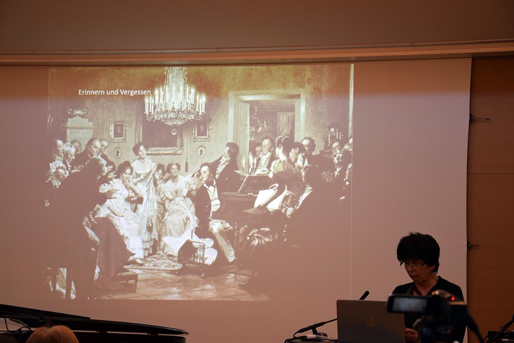 Ingeborg Harer vor einer Folie ihrer Power Point Präsentation zu Anna Fröhlich – Sängerin, Pianistin, erste Professorin