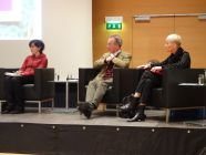 Foto: Bild vom Podium, auf dem drei Leute sitzen und reden/diskutieren