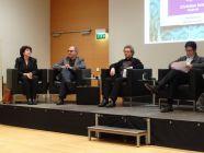 Foto: Bild vom Podium, auf dem vier Leute sitzen und reden/diskutieren