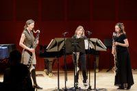Bild von der Bühne: Drei Musikerinnen stehen mit einer Bassklarinette auf der Bühne