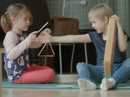 Zwei Kinder spielen Triangel und Kantele