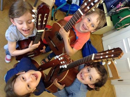 Vier Kinder stehen im Kreis und jedes hat eine Gitarre in der Hand