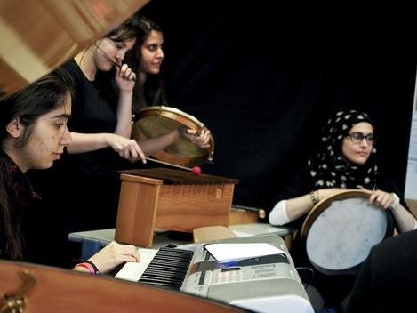 Jugendliche musizieren gemeinsam mit Handtrommeln, Xylophon und E-Piano