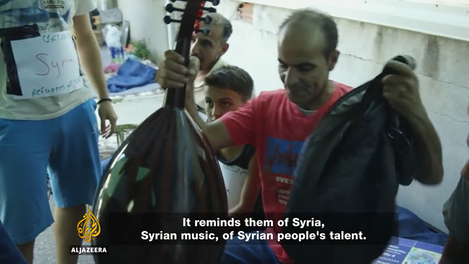 """Figure 10 – A man performing the oud in """"Oreokastro"""" refugee camp, screenshot from Al-Jazeera's documentary """"Refugees got Talent,"""" by Theopi Skarlatos, March 2017. On-line: https://www.aljazeera.com/programmes/witness/2017/03/refugees-talent-170323115635234.html  [03.08.2020]."""