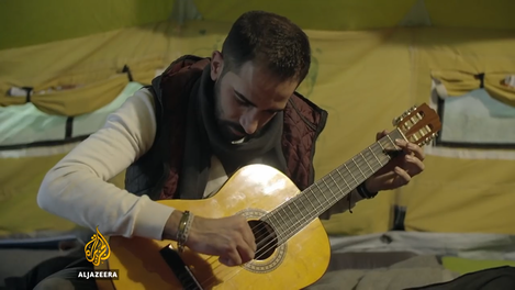 """Figure 11 – A man performing the guitar in """"Oreokastro"""" refugee camp, screenshot from Al-Jazeera's documentary """"Refugees got Talent,"""" by Theopi Skarlatos, March 2017. On-line: https://www.aljazeera.com/programmes/witness/2017/03/refugees-talent-170323115635234.html  [03.08.2020]."""