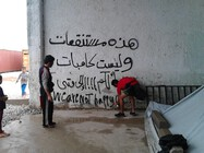 """Figure 2 – A young man writing slogans on the wall of the camp. Picture from """"Softex"""" refugee camp, Thessaloniki, 2016, photo by Ioannis Christidis."""