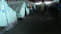 """Figure 3 – Tents inside """"Oreocastro"""" old warehouse converted into refugee camp. Slightly can be seen the word """"tomb"""" written on the tent. Residents of the camp compared the camp with a cemetery. Thessaloniki, 2016, photo by Ioannis Christidis."""