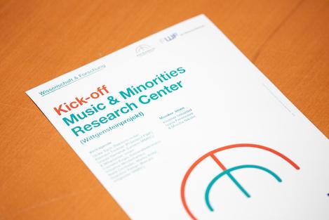 """Veranstaltungsflyer, der das Logo des MMRC zeigt, das ein stilisiertes rostrotes """"m"""" über einem türkisen """"m"""" zeigt, darunter in Schwarz der Schriftzug  """"Music & Minorities Research Center"""""""