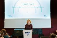 Ulrike Sych am Redner_innenpult