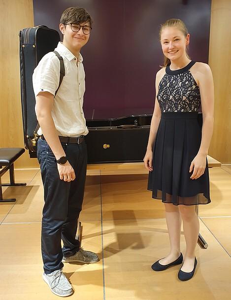 Die beiden Preisträger_innen Katharina Auer (links) und Maxim Tzekov (rechts) mit den jeweiligen Geigenkoffern, gesponsort der Firma Musafia und Herr Univ.Prof, Lothar Strauß.