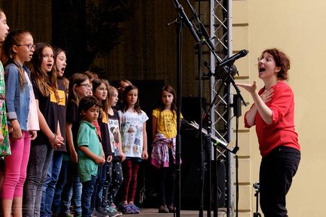 Campusfest 2016 - bunt gekleidete Kinder auf einer Bühne, die Chorleiterin animiert sie sehr aktiv