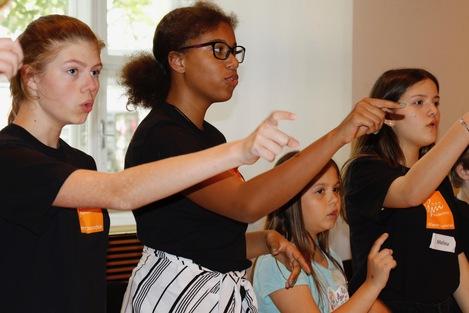 Probe 2018 - Vier Mädchen beim Einsingen zeigen auf den dirigenten