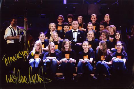Robbie Williams 2014 - Kinderchor singt, Robbie Williams sitz in der Mitte der Kinderschaar und singt mit ihnen
