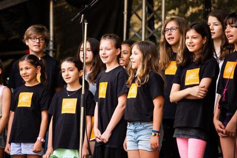 Campusfest 2018 - Kinder im ChorTShirt (schwarz mit orangem Logo) singen fröhlich
